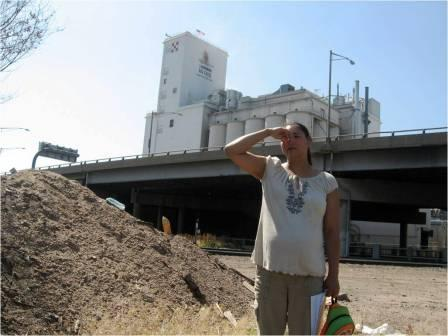 A woman in the Elyria neighborhood holds her nose due to foul odors from nearby factories.