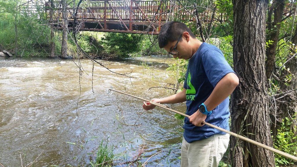 Blue Team member Fernando Chavez collecting a water sample from the Bear Creek in Sheridan