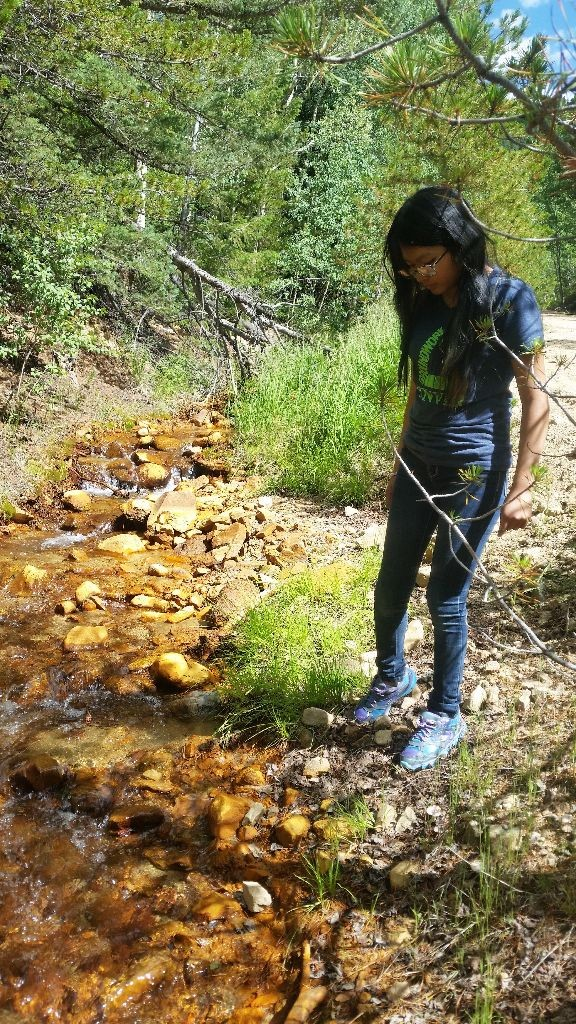 Blue Team member Diana Blanco peering into a creek in Empire, CO